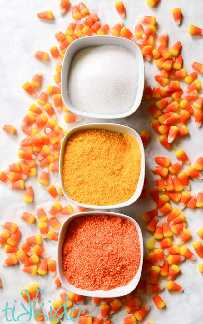 White, yellow, and orange sugar for making cotton candy, surrounded by candy corn candies.