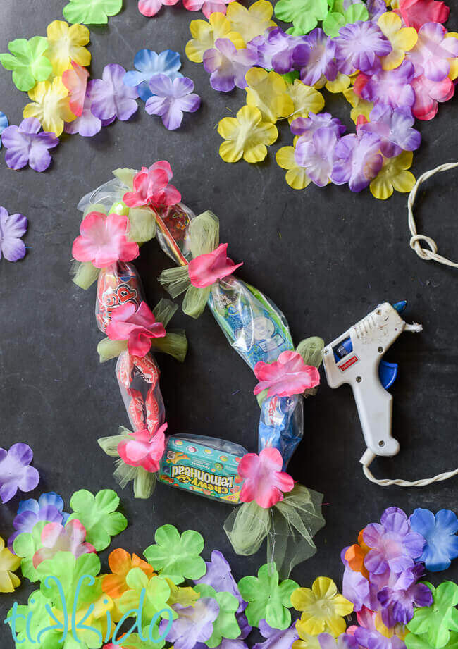 Candy hawaiian lei tutorial tikkido candy lei surrounded by silk flowers with pink silk flowers being glued to the tulle mightylinksfo