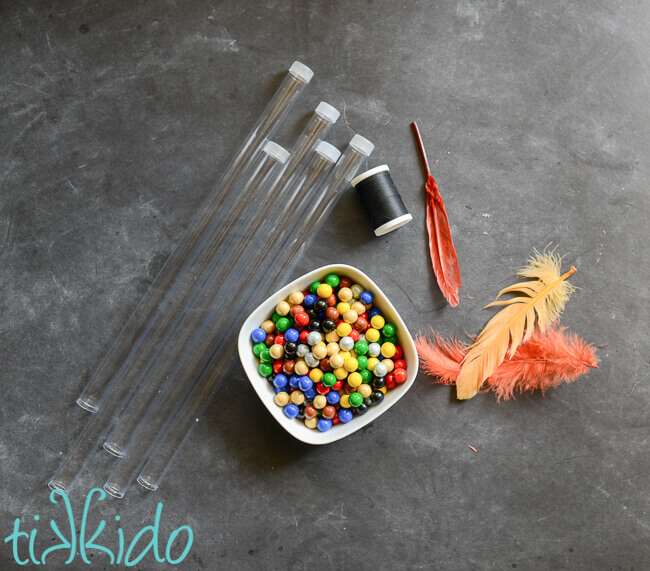 Five long and narrow clear plastic tubes, a spool of black thread, three feathers, and a small white bowl full of round, colorful chocolates.