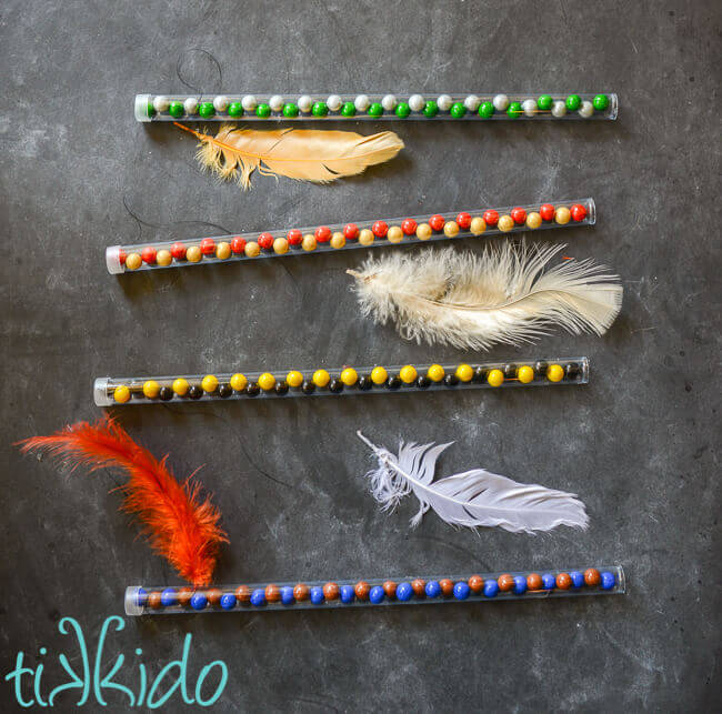 Four clear plastic candy wands filled with Hogwarts house colors chocolate candies, feather attached with black thread to the top of each wand.