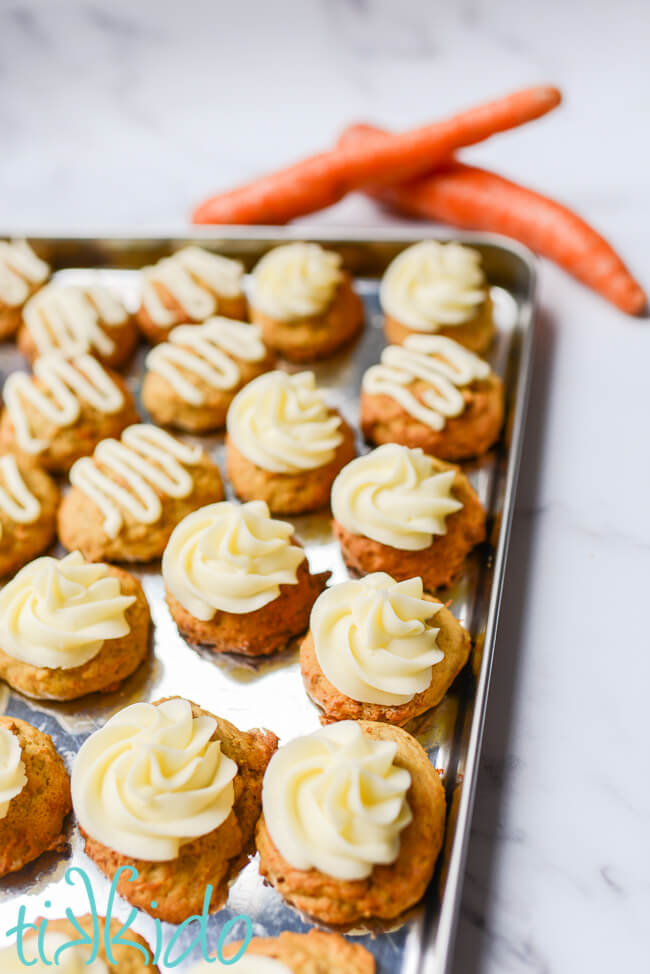 Baking tray filled with carrot cake cookies topped with cream cheese icing.