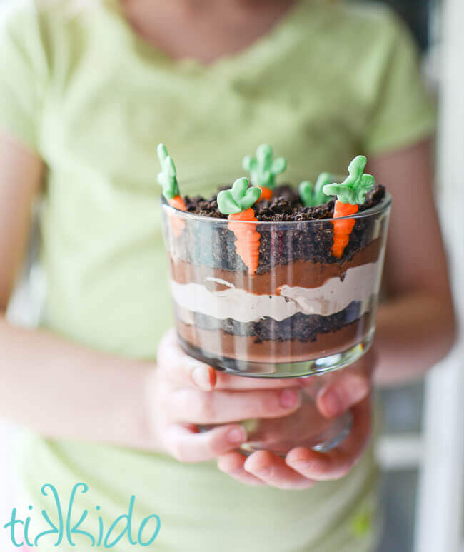 miniature trifle dishe filled with layers of chocolate pudding, chocolate whipped cream, and crushed oreo dirt, with white chocolate carrots planted in the top layer. Held by a girl wearing a light green shirt.