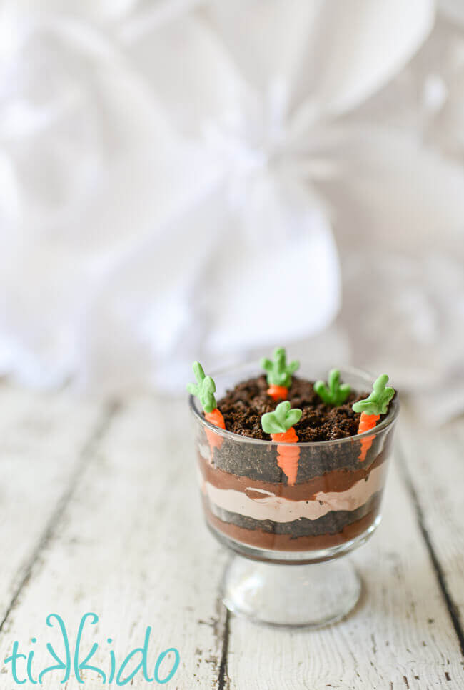 Two miniature trifle dishes filled with layers of chocolate pudding, chocolate whipped cream, and crushed oreo dirt, with white chocolate carrots planted in the top layer.