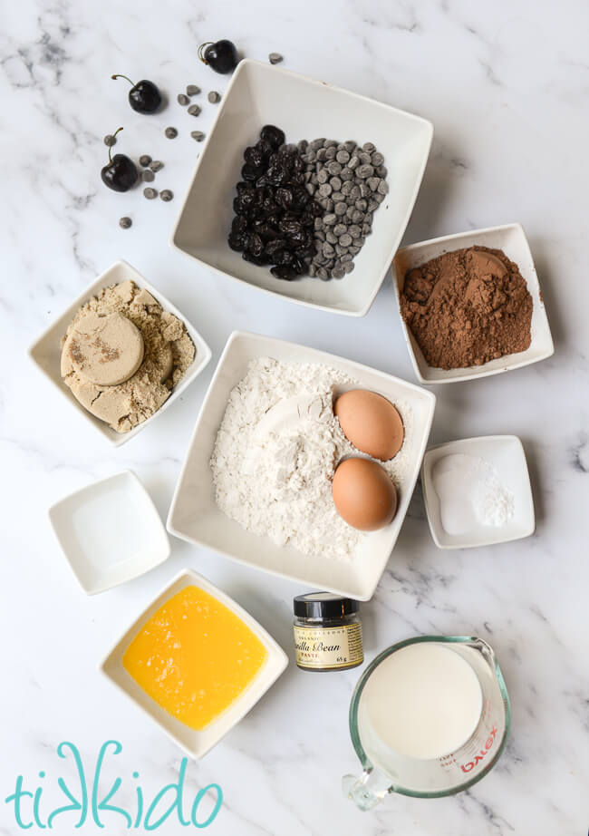 Ingredients for chocolate cherry muffins on a marble surface.
