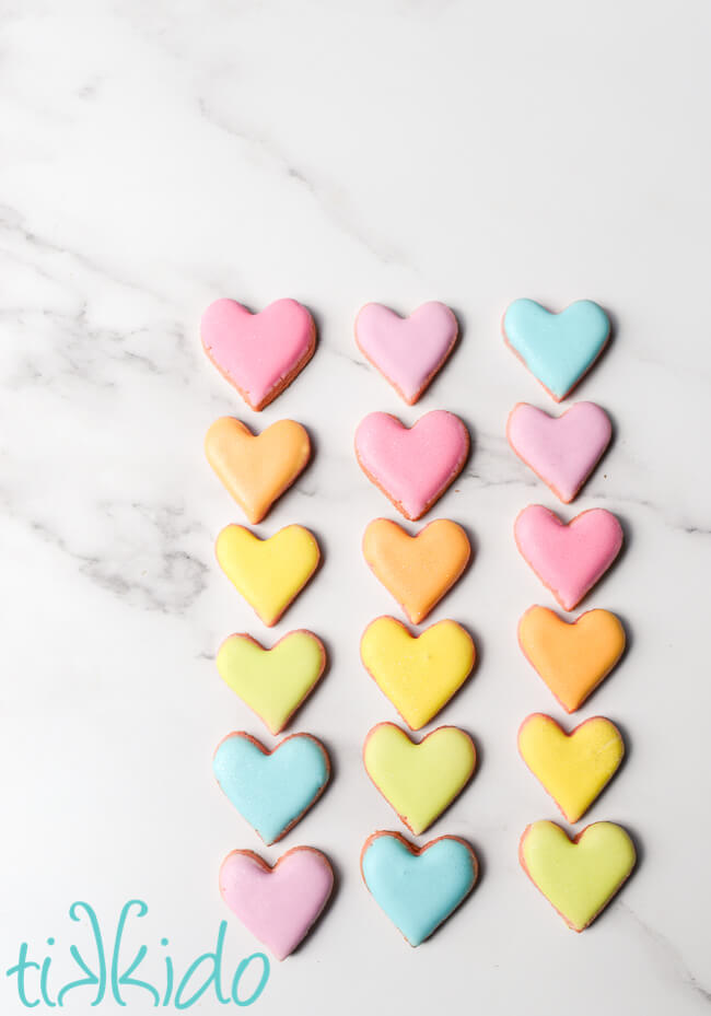 Mini sugar cookies that look like conversation hearts Valentine's day candies on a marble surface.