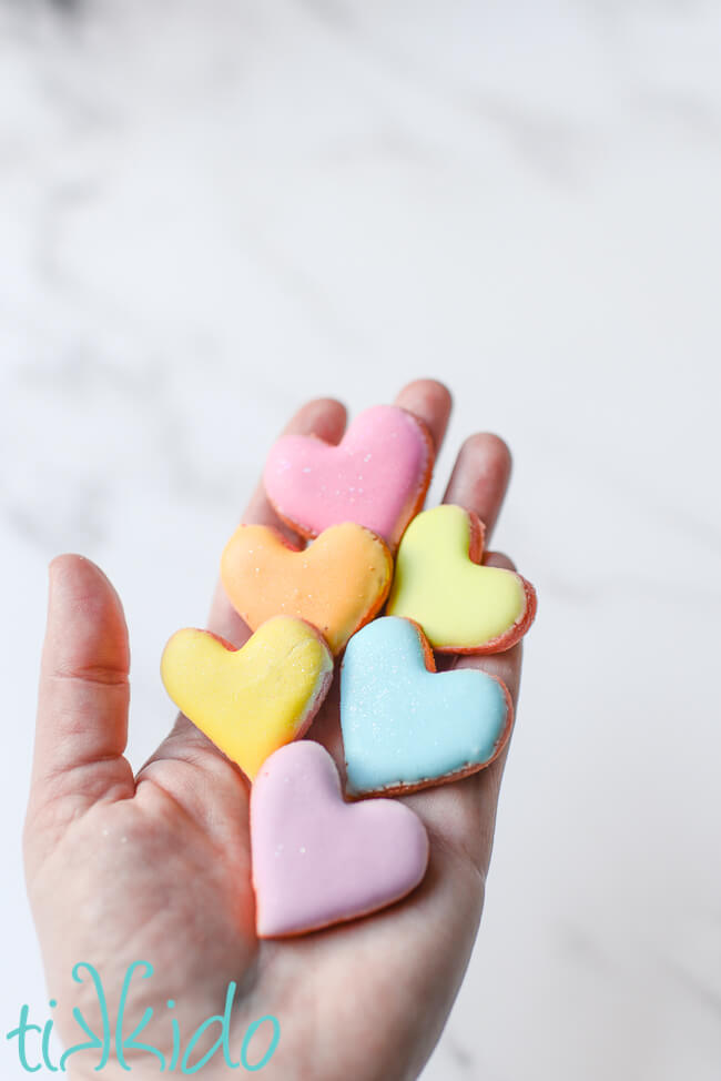 A hand holding six small conversation heart sugar cookies.
