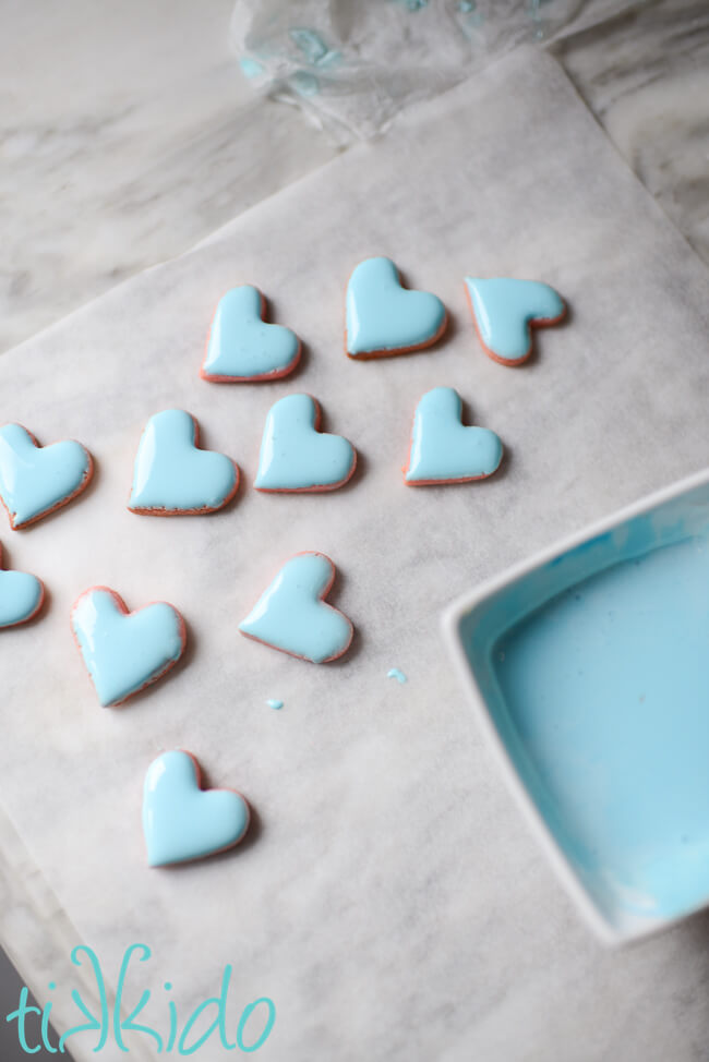 Mini heart cookies coated in light blue royal icing to make Conversation Heart Sugar Cookies