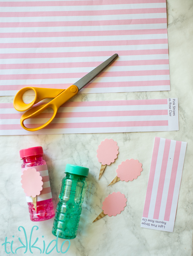 Scrapbook paper being used to decorate bubbles for favors for a cotton candy birthday party.