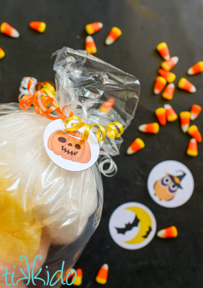 Jack-o-lantern Halloween gift tag on a bag of cotton candy, tied on with curling ribbon.