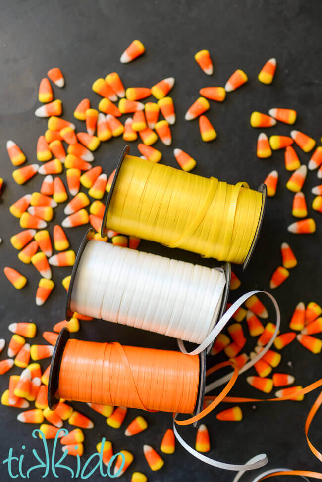 Yellow, white, and orange spools of curling ribbon on a black chalkboard background, surrounded by candy corn candies.