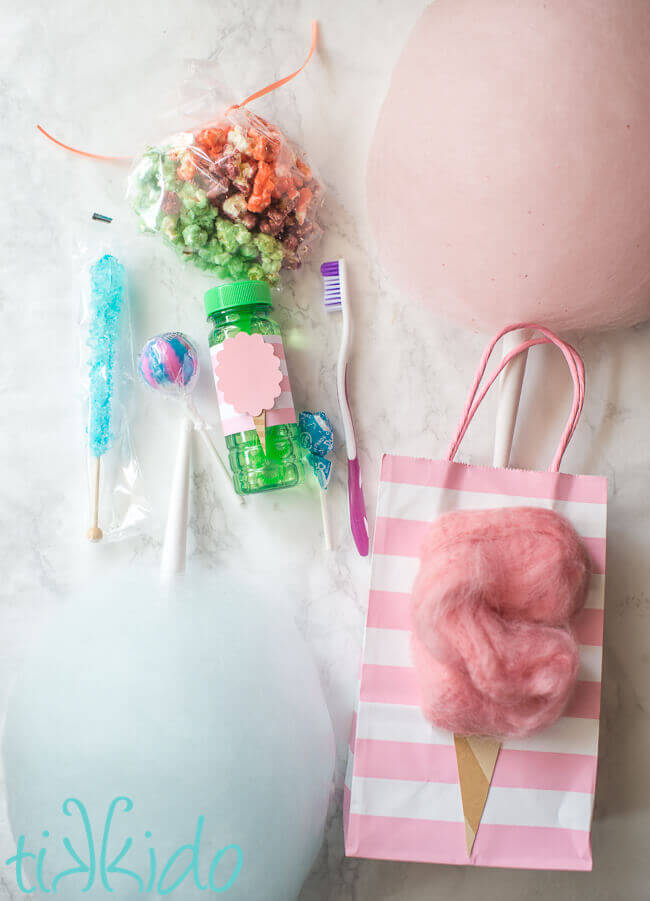 Cotton candy favors for a cotton candy birthday, including cotton candy popcorn, cotton candy lollipops, and a toothbrush.