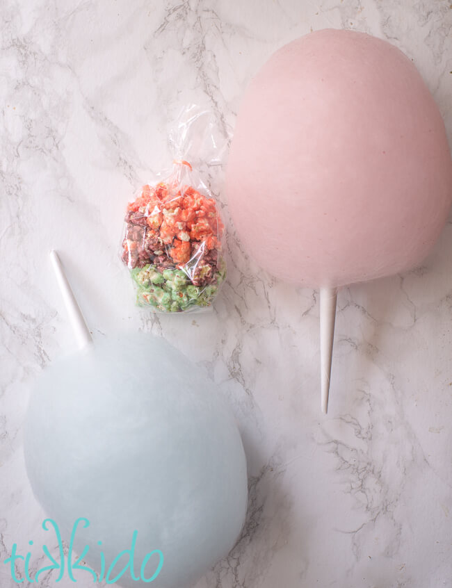 bag of pink, purple, and blue cotton candy popcorn next to two cotton candy cones.