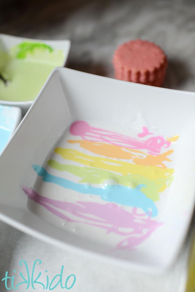 A pastel rainbow of royal icing in a white bowl for making marbleized royal icing decorated sugar cookies.