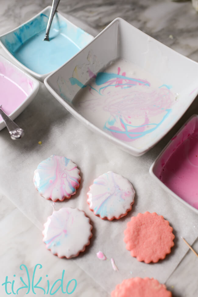 Cotton candy cookies being decorated with marbleized pink, blue, and purple royal icing.