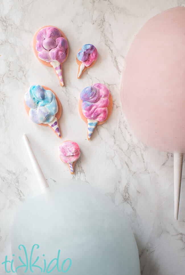 Cotton Candy Cookies decorated with royal icing, next to cones of cotton candy.