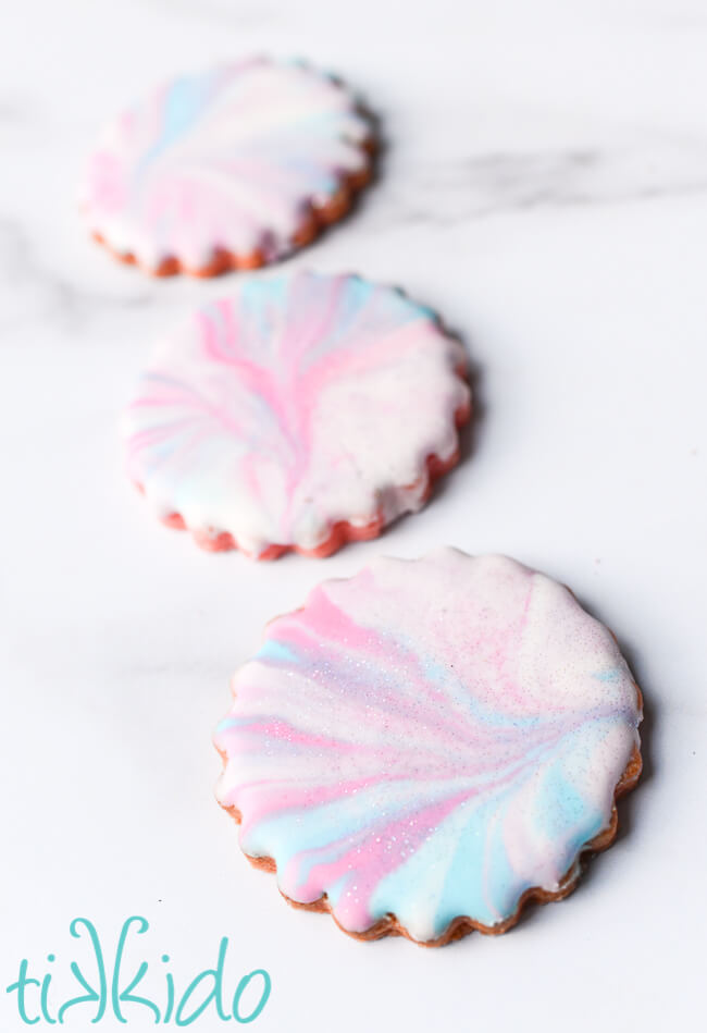 Cotton candy cookies decorated with marbleized pink, blue, and lavender royal icing.