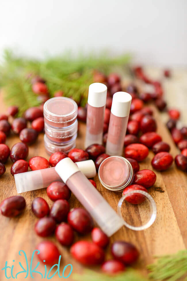 Pots and twist up containers of homemade cranberry lip gloss surrounded by fresh cranberries and evergreen branches.