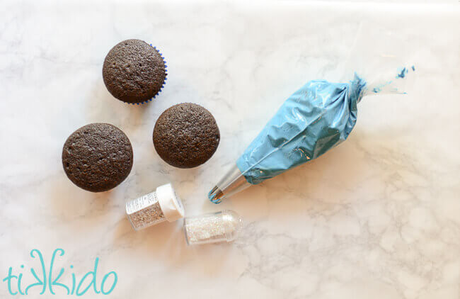 unfrosted chocolate cupcakes and a bag of blue icing