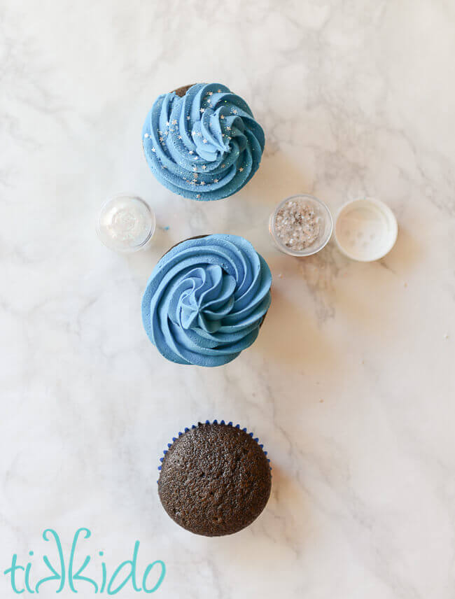 three cupcakes in stages of being iced with blue frosting and sprinkled with edible silver stars