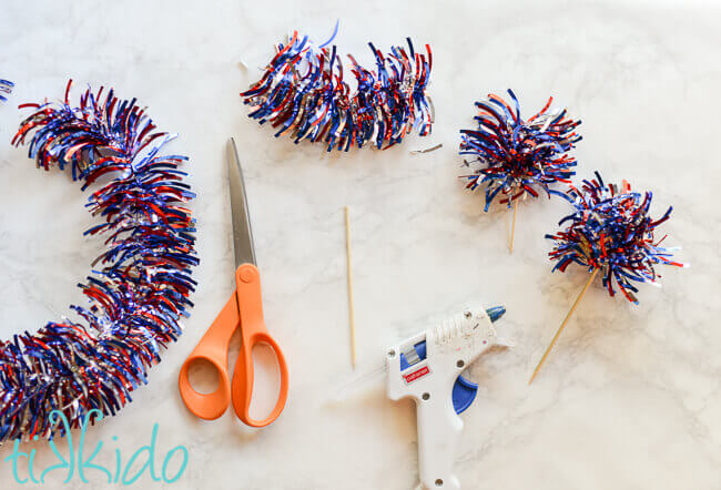patriotic tinsel garland being cut and glued into fireworks cupcake toppers