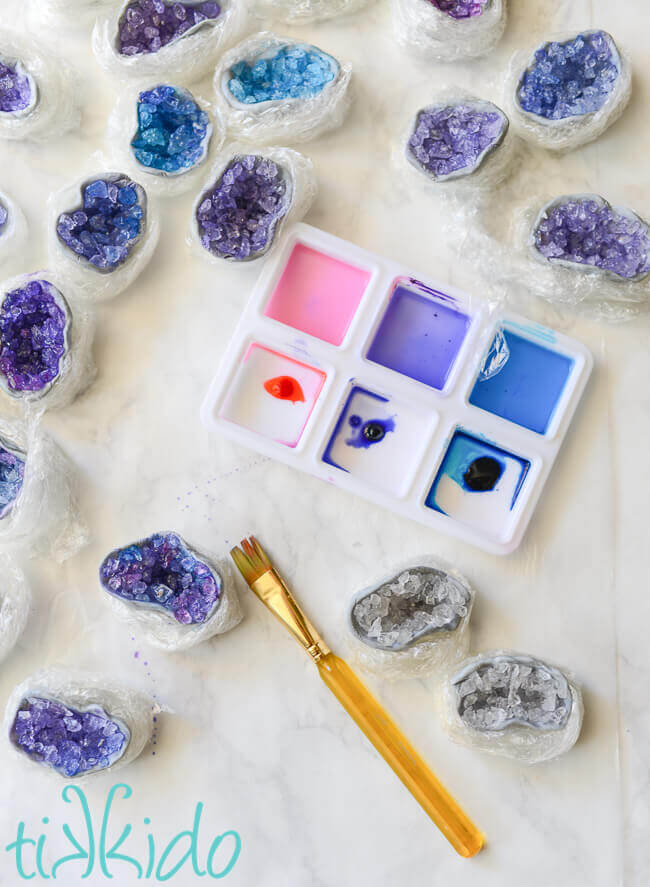 Clear sugar crystal and gum paste geode cupcake toppers being painted with pink, purple, and blue food coloring.
