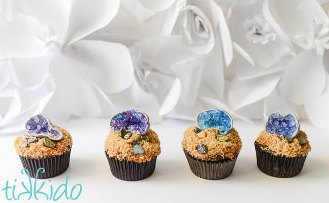 line of four cupcake topped with edible gum paste and sugar crystal geode cupcake toppers on a white background.