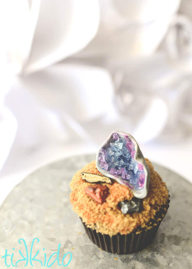 Cupcake topped with brown sugar dirt, chocolate rocks, and a gum paste and rock candy edible geode cupcake topper.