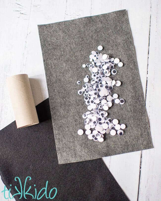 Materials for DIY napkin rings for Halloween made from felt and googly eyes.