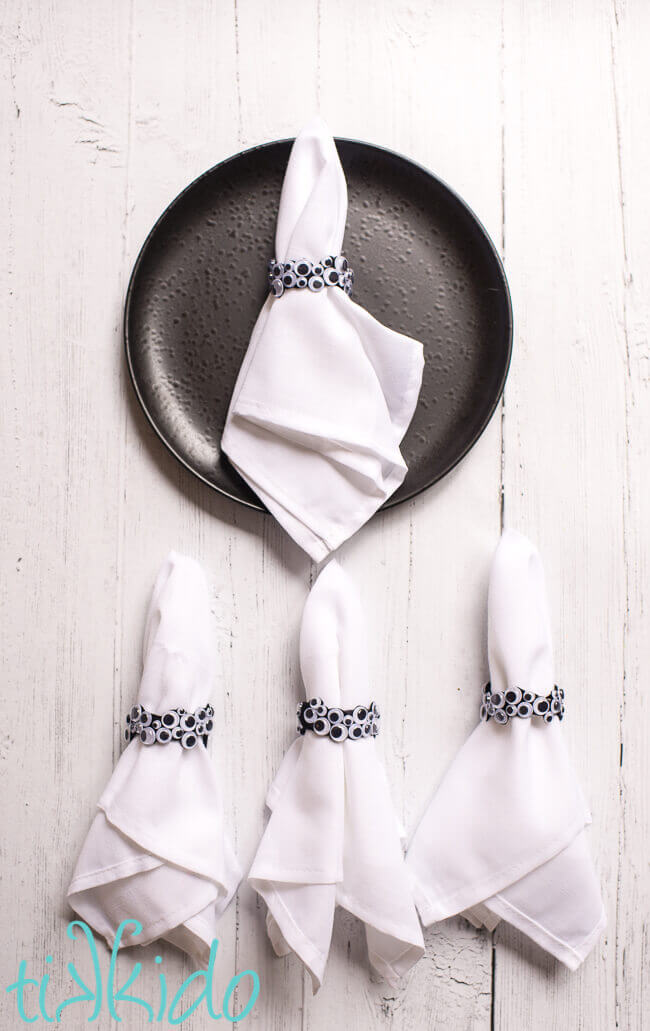 DIY napkin rings made of googly eyes for Halloween on white napkins.