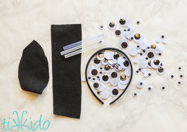 Materials for making a Googly eyes Halloween headband on a white marble surface.