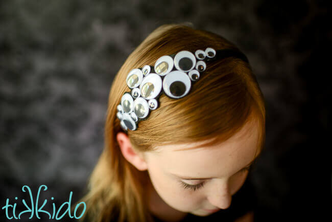 Girl wearing a Googly eyes Halloween headband.