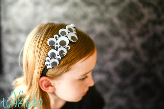 Little girl wearing a Googly eyes Halloween headband.
