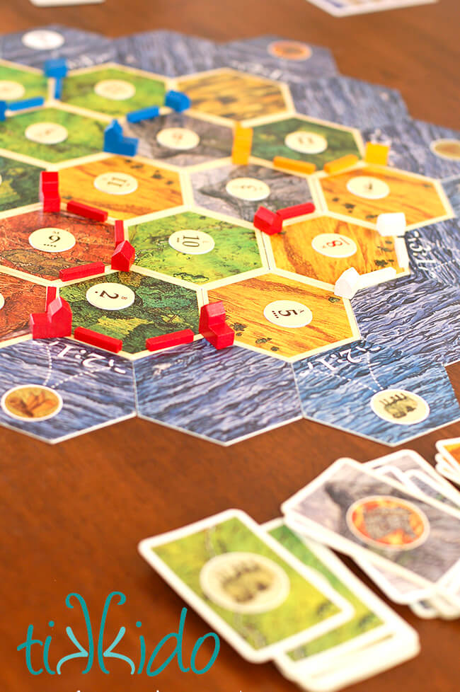 Settlers of Catan board game set up on a wooden table.