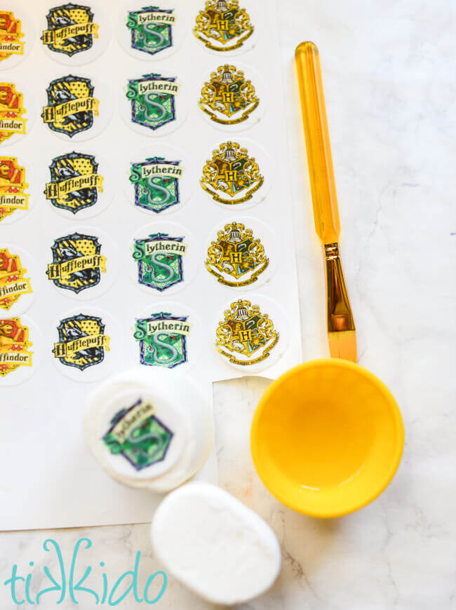 Harry Potter house crest edible images being put on marshmallows.