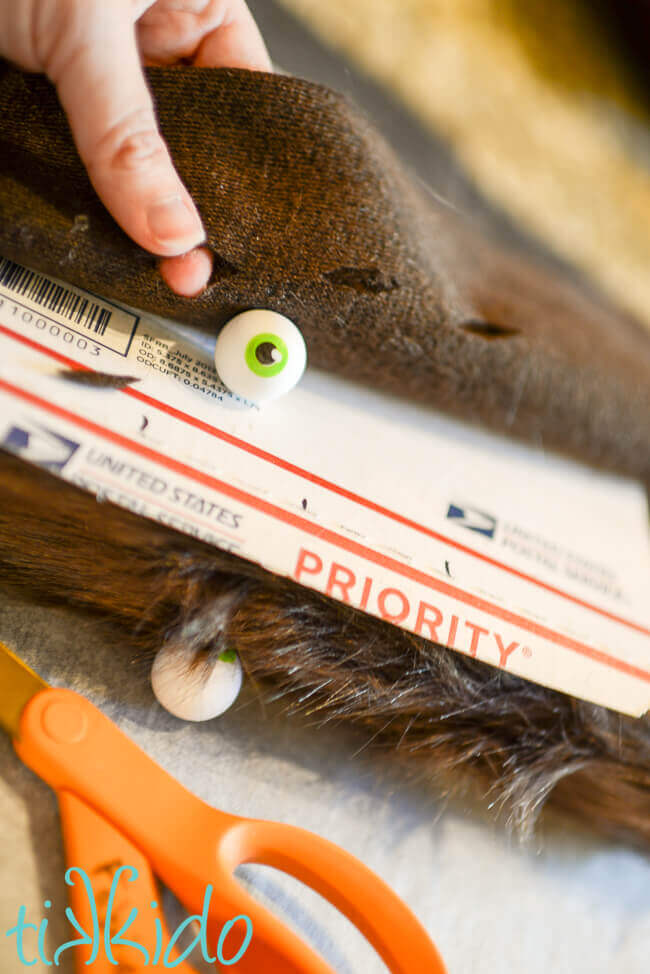 Holes in fake brown fur being cut for the eyeball erasers on the Monster Book of Monsters Box.