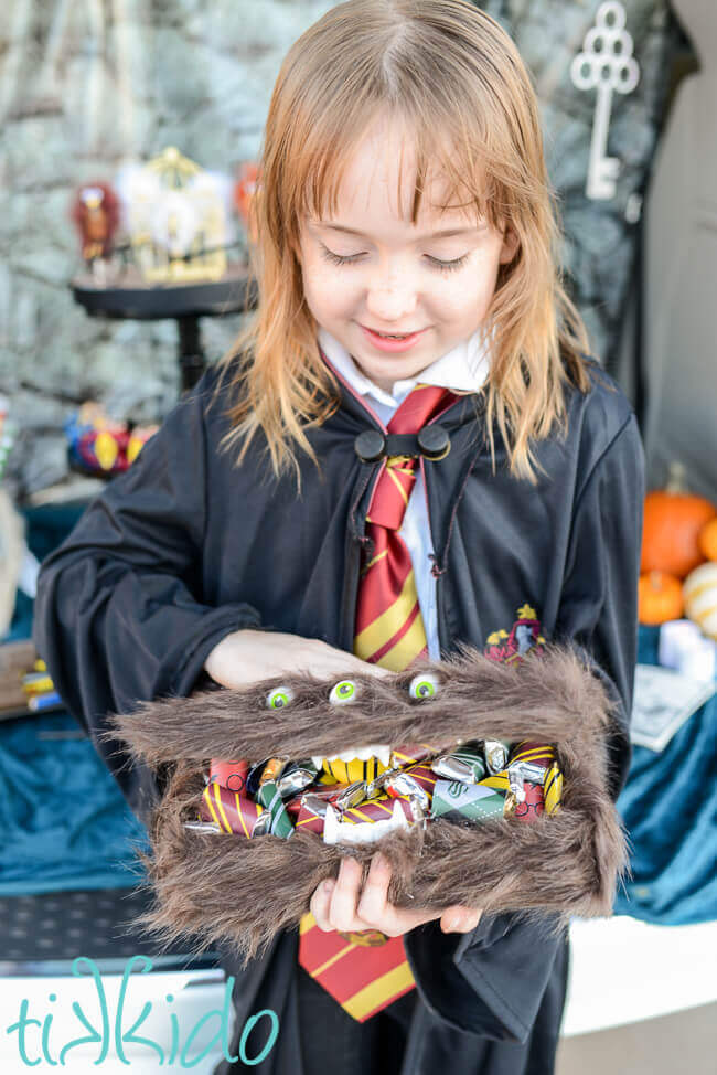 Harry Potter Monster book of Monsters box filled with Harry Potter candies, held by a girl dressed in Hogwarts Robes