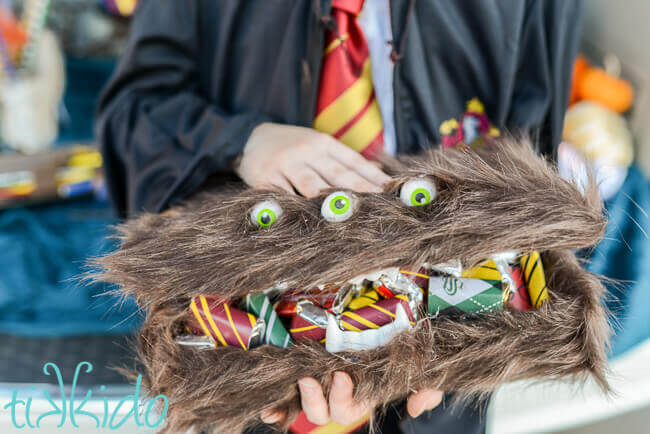 Harry Potter Monster book of Monsters box filled with Harry Potter candies, in the hands of a girl wearing Hogwarts robes.