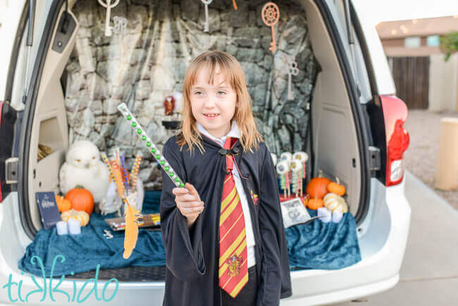 Child holding candy wand filled with green and silver Slytherin colors candies, with a feather appearing to levitate in front of the wand.