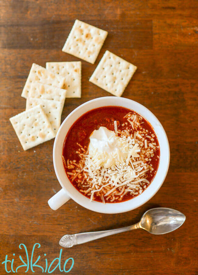 No bean Instant Pot chili in a white bowl topped with sour cream and shredded cheese, surrounded by saltine crackers and a spoon.