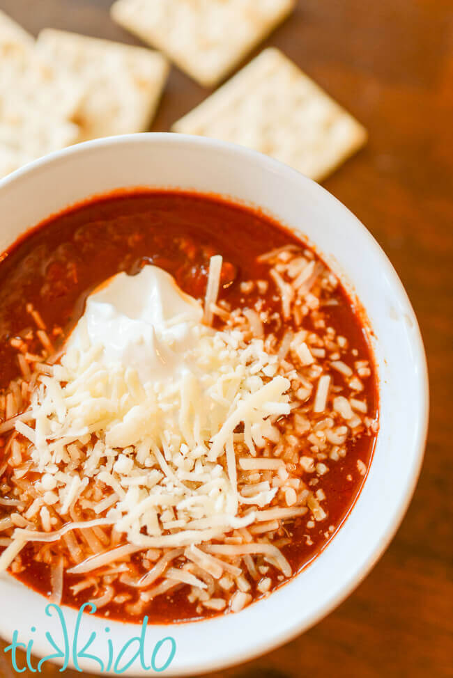 Instant pot no bean chili in a white bowl topped with sour cream and shredded cheese
