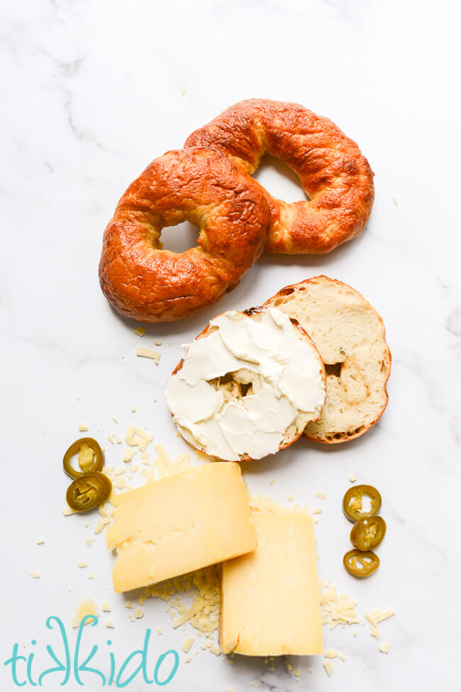 Three Jalapeño Cheddar Bagels, one sliced and spread with cream cheese, next to cheddar cheese and Jalapeño slices.