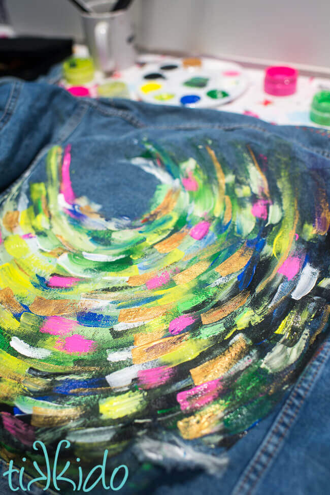 Painted denim jacket painted with bright acrylic paints in an abstract, swirling pattern.