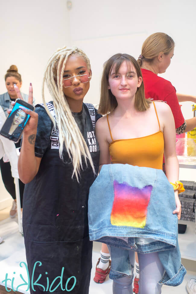 Artist Jade Laurice and a young woman holding a painted denim jacket.