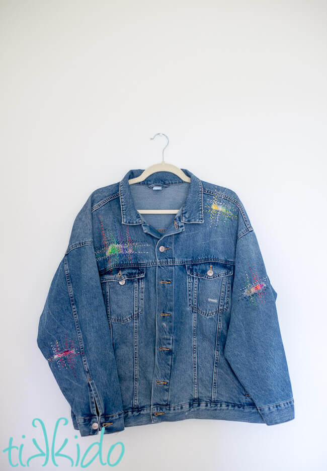 Jean jacket with holes patched with sashiko mending, creating beautiful visible mending embellishments.