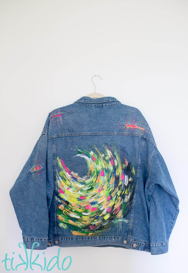 Brightly painted denim jacket on a white background.