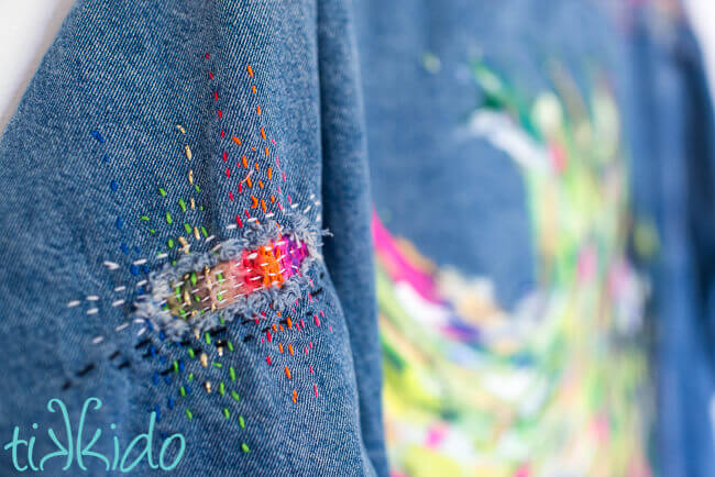 Hole in the arm of a jean jacket patched with colorful Sashiko mending.