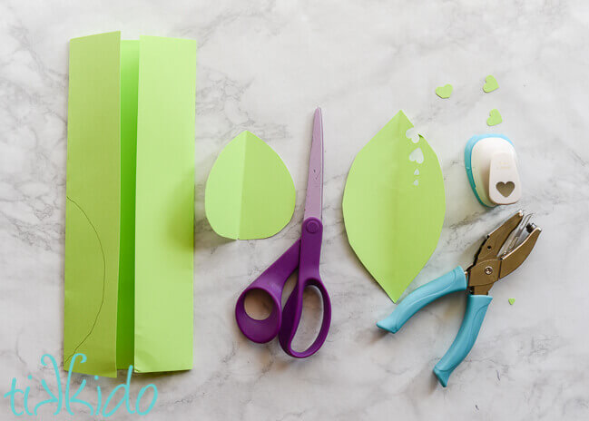 Piece of folded green paper, green paper cut into a leaf shape, scissors, and heart shaped paper punches on white marble background