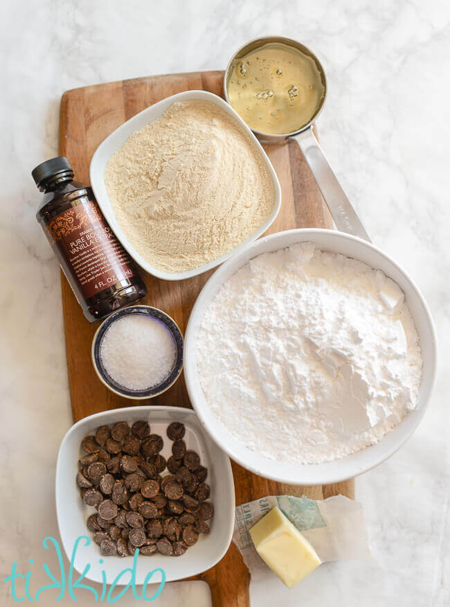 Ingredients for chocolate malt tootsie roll candies on a wooden cutting board on a white marble background