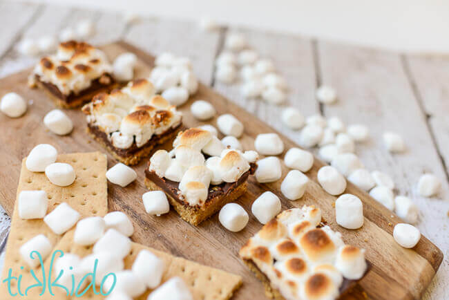 No bake s'mores bar squares on a wooden cutting board.