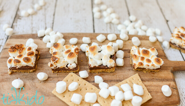 S'mores bar cookies on a wooden cutting board.